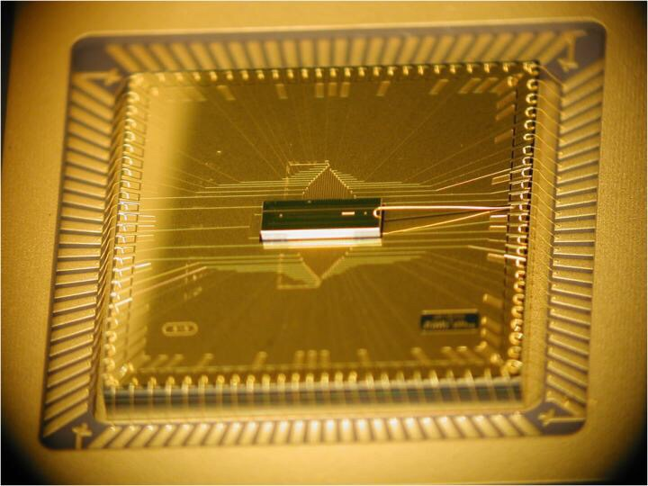 CAPTION A photograph of the completed BGA trap assembly. The trap chip is at the center, sitting atop the larger interposer chip that fans out the wiring. The trap chip surface area is 1mm x 3mm, while the interposer is roughly 1 cm square. CREDIT D. Youngner, Honeywell