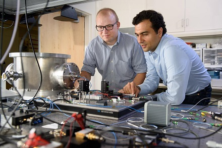 CAPTION Post-doctoral scholar Peter McMahon, left, and visiting researcher Alireza Marandi examine a prototype of a new type of light-based computer. CREDIT L.A. Cicero