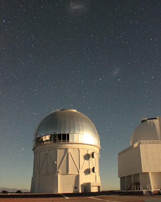The Víctor M. Blanco Telescope at the Cerro Tololo Inter-American Observatory in Chile, where the Dark Energy Camera is being used to collect image data for the DECam Legacy Survey. The glint off the dome is moonlight; the small and large Magellanic clouds can be seen in the background. (Image: Dustin Lang, University of Toronto)